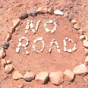 """Rocks on the ground formed into a sign saying, """"No Road""""."""