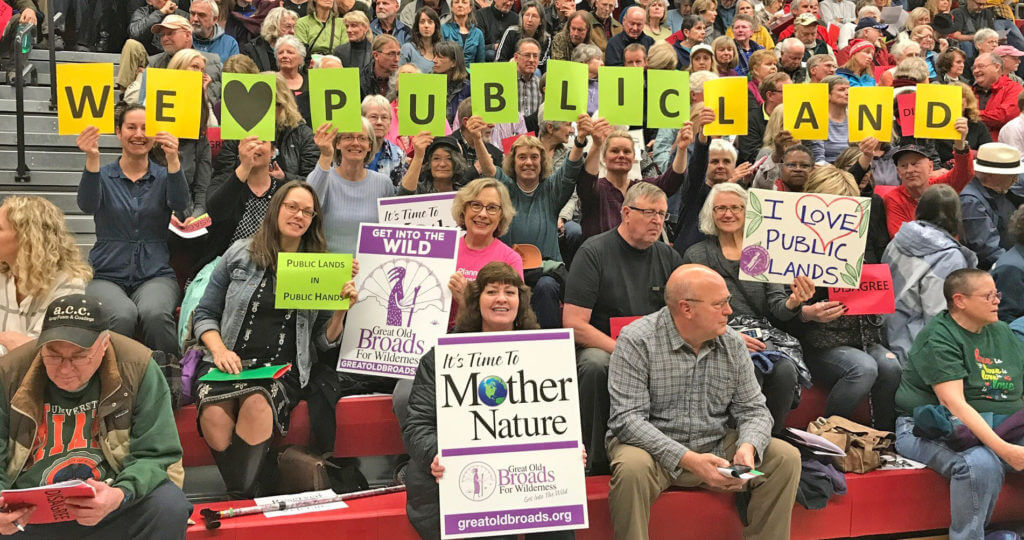 A group of broads showing their support in preserving public lands by holding signs