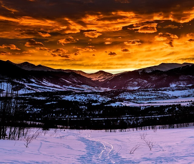 A scenic picture of a snowed in meadow with mountains in the background during sunset hour