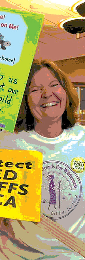 A woman in a Great Old Broads shirt smiling with signs