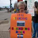 """Woman holding """"Still standing, Standing Rock"""" sign at a No DAPL rally"""
