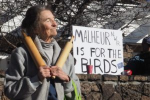 """Woman protesting with a sign behind her stating """"Malheur is for the birds"""""""