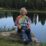 Woman sitting on a rock next to a lake