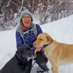 Woman kneeling with two dogs in the snow